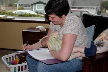 Baby M nursing while mom writes notes in her Reiki binder.  Multi tasking is not new to moms.